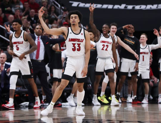 Keith Oddo (1) celebrates with teammates after a Jordan Nwora 3-pointer against Virginia at the Yum Center on Feb. 8, 2020.