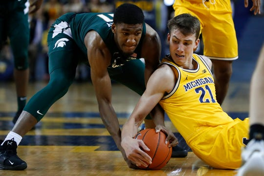 Michigan State forward Aaron Henry (11) and Michigan guard Franz Wagner (21) battle for a loose ball in the first half of an NCAA college basketball game in Ann Arbor, Mich., Saturday, Feb. 8, 2020. (AP Photo/Paul Sancya)