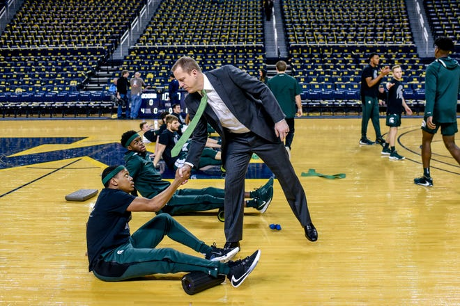Michigan State's associate head coach Dane Fife, right, shakes Cassius Winston's hand before the Spartans game against Michigan on Saturday, Feb. 8, 2020, at the Crisler Center in Ann Arbor.