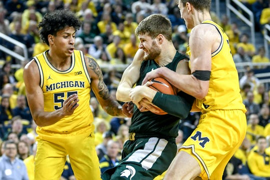 Michigan State's Kyle Ahrens, center, battles for possession of the ball with Michigan's Franz Wagner, right, and Eli Brooks during the second half on Saturday, Feb. 8, 2020, at the Crisler Center in Ann Arbor.