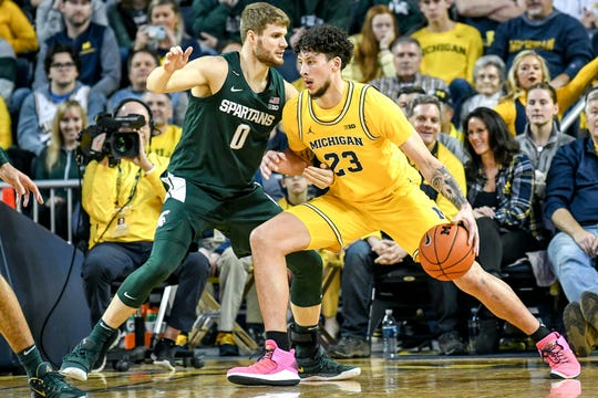 Michigan State's Kyle Ahrens, left, guards Michigan's Brandon Johns Jr. during the second half on Saturday, Feb. 8, 2020, at the Crisler Center in Ann Arbor. Johns played high school basketball at East Lansing.
