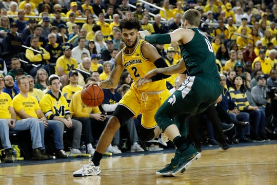 Feb 8, 2020; Ann Arbor, Michigan, USA; Michigan Wolverines forward Isaiah Livers (2) dribbles defended by Michigan State Spartans guard Kyle Ahrens (0) in the first half at Crisler Center. Mandatory Credit: Rick Osentoski-USA TODAY Sports