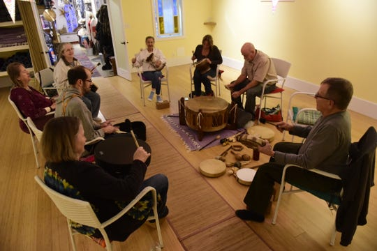 Members of the First Friday Drum Circle beat in rhythm at Mind Body Align downtown Mansfield.