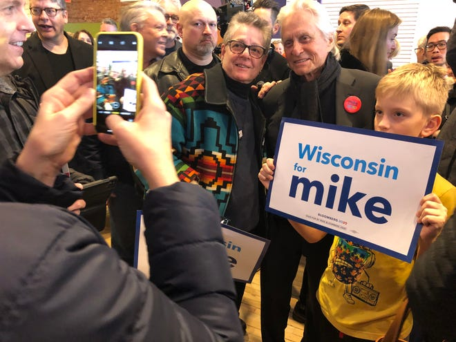 Actor Michael Douglas takes a photo with supporters for Michael Bloomberg at the Madison campaign office on Saturday.