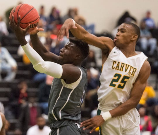 Lanier's Antwan Burnett (11) goes up for a layup  guarded by Carver's Mike Murray (23) during the Class 6A, Area 4 championship at Carver High School in Montgomery, Ala., on Friday, Feb. 7, 2020.