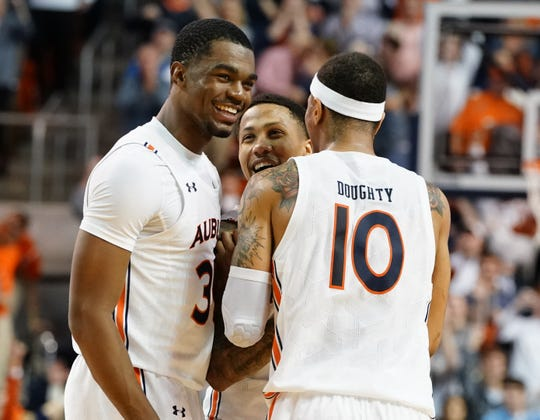 Feb 8, 2020; Auburn, Alabama, USA; Auburn Tigers guard J'Von McCormick (5) reacts with Auburn Tigers guard Devan Cambridge (35) and  guard Samir Doughty (10) after hitting the winning shot in overtime against LSU Tigers the at Auburn Arena. Mandatory Credit: Marvin Gentry-USA TODAY Sports