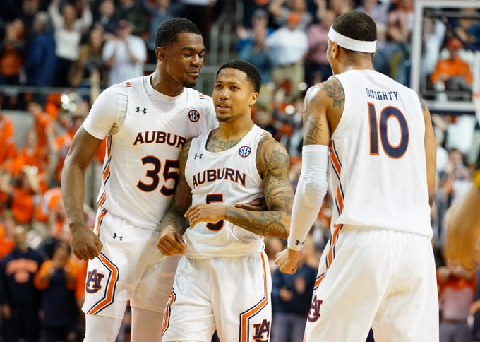 Auburn guard J'Von McCormick (5) celebrates with Devan Cambridge (35) and Samir Doughty (10) after hitting the winning shot in overtime against LSU on Feb. 8, 2020, in Auburn AL.