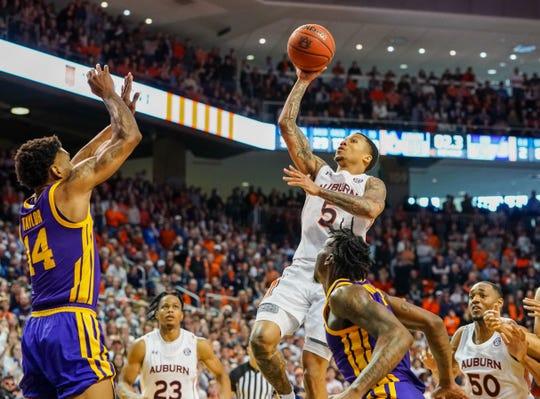 Auburn guard J'Von McCormick (5) hits the game-winning shot over LSU guard Marlon Taylor (14) at Auburn Arena on Feb. 8, 2020.
