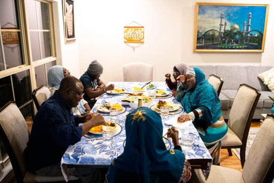 Metro Council member Zulfat Suara (right) eats dinner with her family at her home Monday, Feb. 3, 2020, in Nashville, Tenn.