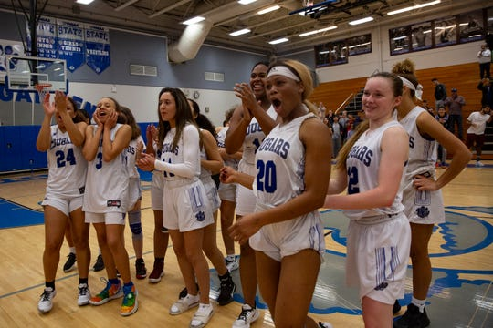 Members of the Barron Collier High School girls basketball team celebrate3s after beating Naples High School 51-40 to win the Class 5A-District 12 championship, Friday, Feb. 7, 2020, at Barron Collier High School.
