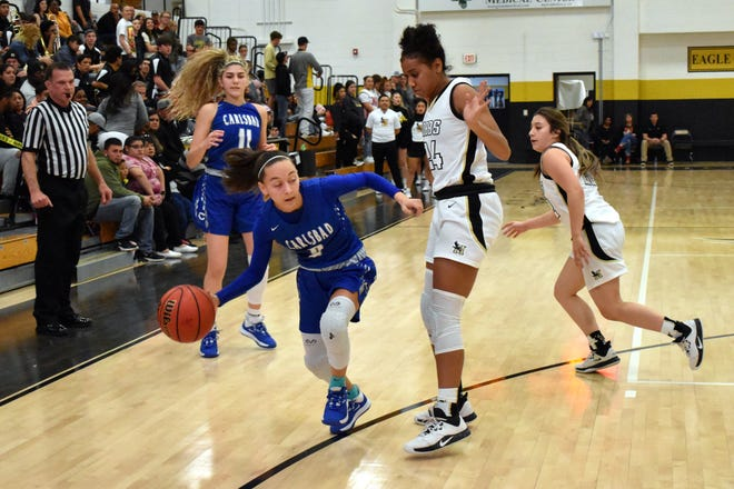 Carlsbad point guard Baylee Molina gets around Hobbs' Elise Turrubiates in the third quarter in Tasker Arena, Friday night. The Cavegirls fell to the Lady Eagles 43-39.