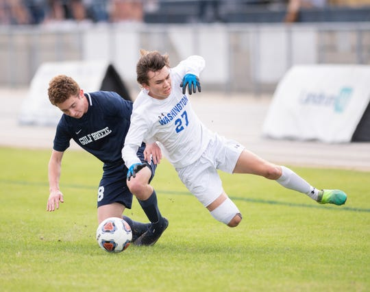 Nick Wilson (18) and Drayton Braddock (27) vie for the ball during the Booker T. Washington vs Gulf Breeze boys soccer district championship soccer game at Gulf Breeze High School on Saturday, Feb, 8, 2020.
