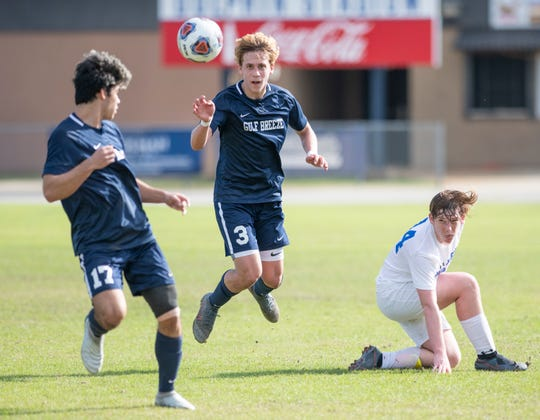Keegan Abell (3) gets the pass to Jayce Dotson (17) despite a sliding Lennon Schweigert (14) during the Booker T. Washington vs Gulf Breeze boys soccer district championship soccer game at Gulf Breeze High School on Saturday, Feb, 8, 2020.