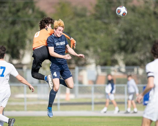 Goal keeper John Michael Guidroz (0) and Alan Quilligan (4) leap for the ball during the Booker T. Washington vs Gulf Breeze boys soccer district championship soccer game at Gulf Breeze High School on Saturday, Feb, 8, 2020.