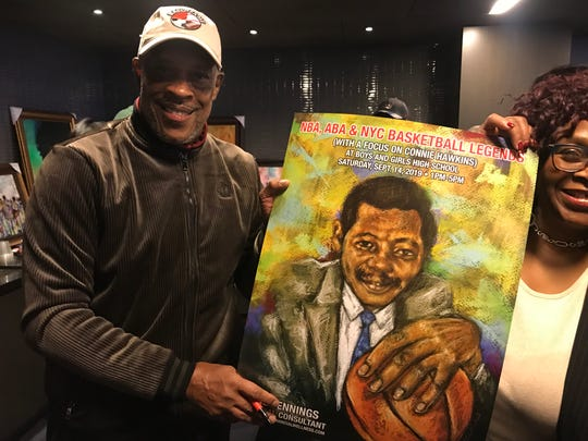 Nate 'Tiny' Archibald poses with an poster of the late, great Connie Hawkins at an event at Barclays Center in Brooklyn before the Brooklyn Nets played the Phoenix Suns on Monday, Feb. 3.