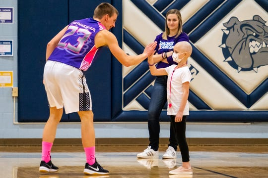 Yale junior Matt McLelland (23) high-fives 7-year-old Brynlee Wing before taking the court for the Coaches vs. Cancer game against Cros-Lex Friday, Feb. 7, 2020, at Yale High School. Brynlee, a second-grader at Avoca Elementary, was diagnosed with neuroblastoma in October 2019.