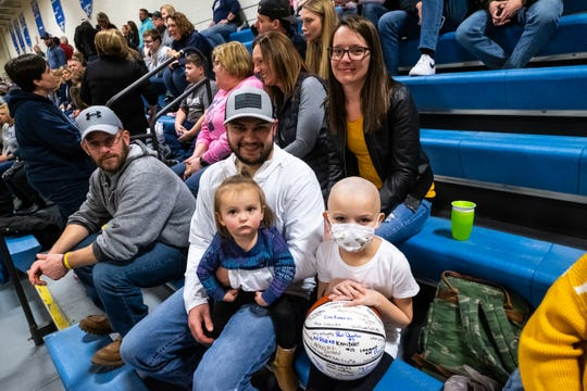 Brynlee Wing, 7, sits with her mother Jessie Wing, back; father Patrick Wing, left, and sister Saylor, 1, during the Coaches vs. Cancer game between Yale and Cros-Lex high schools Friday, Feb. 7, 2020, at Yale High School. Brynlee, a second-grader at Avoca Elementary, was diagnosed with neuroblastoma in October 2019.