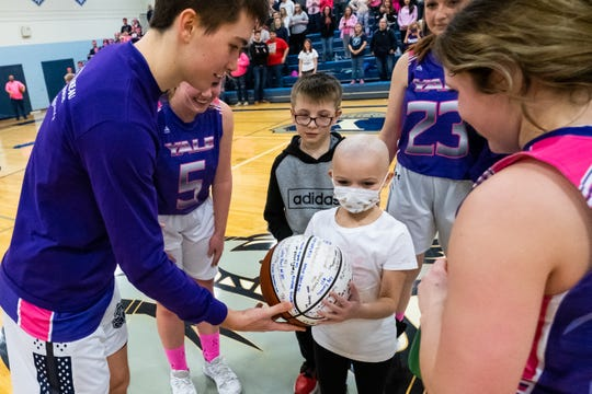 Members of Yale High School's basketball teams present Brynlee Wing, 7, with a signed basketball during the Coaches vs. Cancer game against Cros-Lex Friday, Feb. 7, 2020, at Yale High School. Brynlee, a second-grader at Avoca Elementary, was diagnosed with neuroblastoma in October 2019.