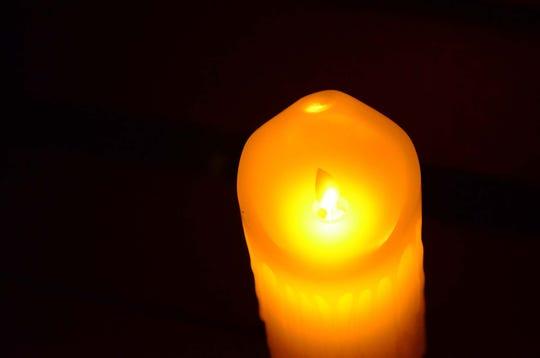 A photo fo a candle at a vigil.