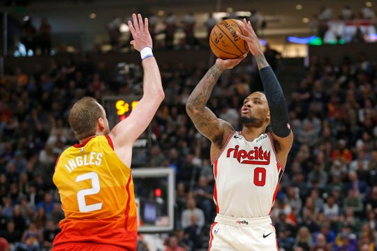 Portland Trail Blazers guard Damian Lillard (0) shoots as Utah Jazz guard Joe Ingles (2) defends during the first half of an NBA basketball game Friday, Feb. 7, 2020, in Salt Lake City.