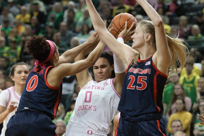 Arizona's Amari Carter, left, and Cate Reese, right, pressure Oregon's Satou Sabally during the second quarter of an NCAA college basketball game in Eugene, Ore., Friday, Feb. 7, 2020.