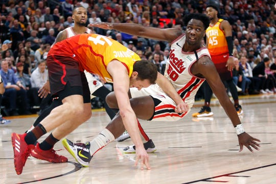Utah Jazz forward Bojan Bogdanovic, left, fouls Portland Trail Blazers forward Caleb Swanigan (50) during the first half of an NBA basketball game Friday, Feb. 7, 2020, in Salt Lake City.