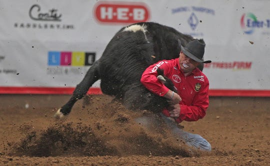 Matt Reeves kicks up a cloud of dirt as he competes in the steer wrestling event at the San Angelo Stock Show and Rodeo on Friday, Feb. 7, 2020.