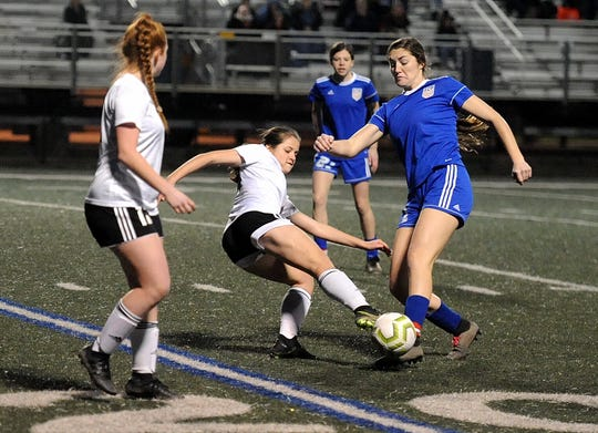 Evangel's Ellie Dubois (right) tries to move the ball against Ouachita C.hristain Friday in the Lady Eagles' LHSAA Division IV playoff soccer game. Evangel won 4-0