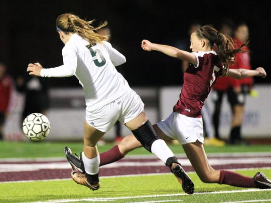 Lincoln senior Sarah Wnuk takes a shot that gets over the leg of Chiles freshman Layla Thompson as Chiles' girls soccer team edged Lincoln in a penalty-kick shootout following 100 minutes of scoreless soccer to capture the District 2-A title on Feb. 7, 2020.