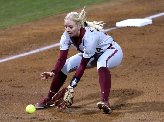 Florida State Seminoles utility player Sydney Sherrill (24) scoops up a ground ball. The Florida State Seminoles beat the Alabama Crimson Tide 8-7 in the eighth inning on Friday, Feb. 7, 2020.