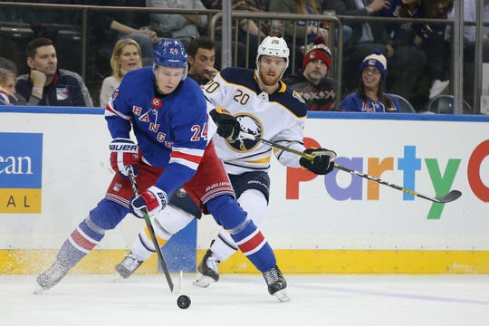 Feb 7, 2020; New York, New York, USA; New York Rangers right wing Kaapo Kakko (24) plays the puck against Buffalo Sabres left wing Scott Wilson (20) during the first period at Madison Square Garden.