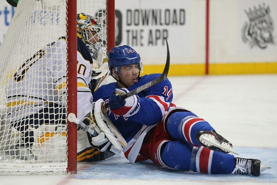 Feb 7, 2020; New York, New York, USA; New York Rangers center Greg McKegg (14) crashes into Buffalo Sabres goalie Carter Hutton (40) during the second period at Madison Square Garden.