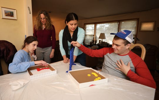 Jennifer Peralta, center, an ABA Therapist, works with Samara Klein, 17 1/2 and Jacob Parsons, 19, as Klein's mother Pam looks on, at a home in Wesley Hills, Feb. 8, 2020.