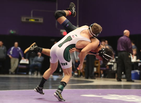 From left, Yorktown's Andrew Finateri flips Clarkstown North's Alexander Pelletier on his way to defeating him in the 120-pound weight class during the divisional wrestling tournament at John Jay High School in Cross River Feb. 8, 2020.