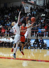 Burkburnett's Jaden Arnold attempts a layup between Hirschi's Kam Hedge (11) and Hirschi's Chris Whitten in District 6-4A action at Hirschi Fieldhouse on Friday, Feb. 7, 2020.