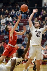 Reed Coconis, of Sheridan, takes a shot over John Glenn's Ben Judd on Friday night in New Concord.
