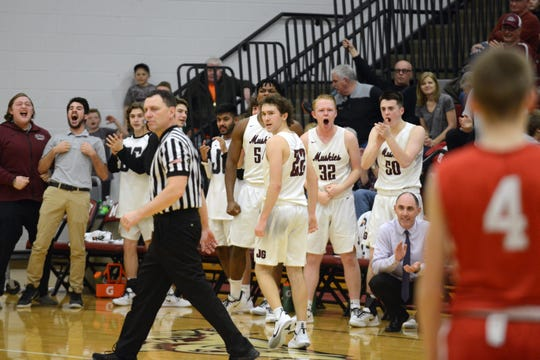 John Glenn's bench celebrates Devan Burris' dunk during the fourth quarter of a 45-34 win against Sheridan on Friday night in New Concord.