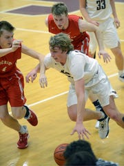 John Glenn's Reece Perkins drives up court against Sheridan's Hunter Yakes, left, and Landen Russell. Perkins had a game-high 16 points in the Muskies' 45-34 win on Friday night in New Concord.
