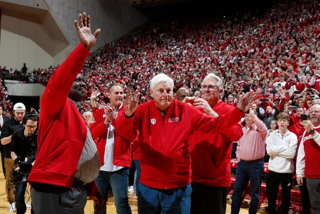 Former Indiana coach Bobby Knight waves to Hoosiers fans at Assembly Hall in Bloomington as he is escorted with his son Pat Knight and former players Quinn Buckner and Steven Green during halftime.