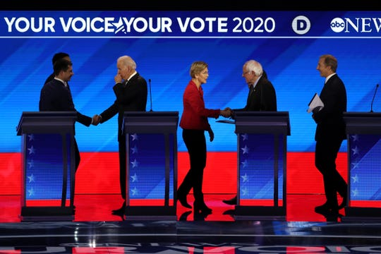 Democratic presidential candidates former South Bend, Indiana Mayor Pete Buttigieg, Andrew Yang, former Vice President Joe Biden, Sen. Elizabeth Warren (D-MA), Sen. Bernie Sanders (I-VT), Sen. Amy Klobuchar (D-MN) and Tom Steyer shake hands at the conclusion of the Democratic presidential primary debate.