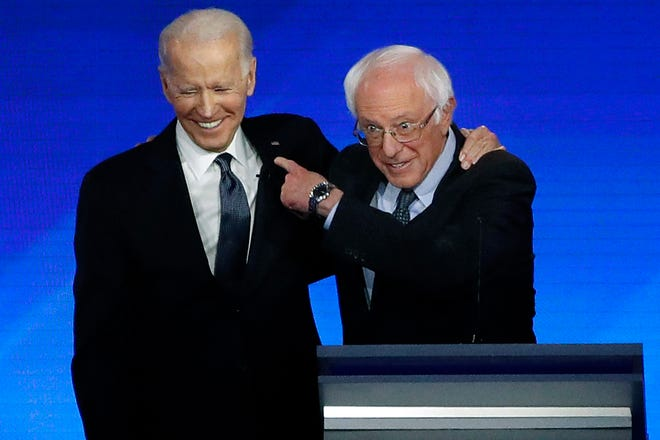 Former Vice President Joe Biden, left, embraces Sen. Bernie Sanders, I-Vt., during a Democratic presidential primary debate, Friday, Feb. 7, 2020, hosted by ABC News, Apple News, and WMUR-TV at Saint Anselm College in Manchester, N.H. (AP Photo/Elise Amendola)