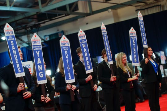 Volunteers hold up signs as they wait for Democratic presidential candidates to enter the media spin room near the end of a Democratic presidential primary debate.
