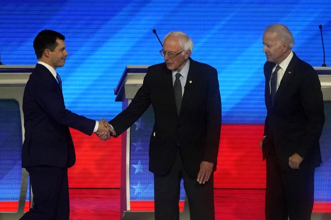 Democratic presidential hopeful former Mayor of South Bend, Indiana, Pete Buttigieg,  shakes hands with Vermont Senator Bernie Sanders, as former Vice President Joe Biden looks on during the eighth Democratic primary debate of the 2020 presidential campaign season co-hosted by ABC News, WMUR-TV and Apple News at St. Anselm College in Manchester, New Hampshire, on February 7, 2020. (Photo by TIMOTHY A. CLARY / AFP) (Photo by TIMOTHY A. CLARY/AFP via Getty Images) ORG XMIT: Eighth De ORIG FILE ID: AFP_1OS7QA