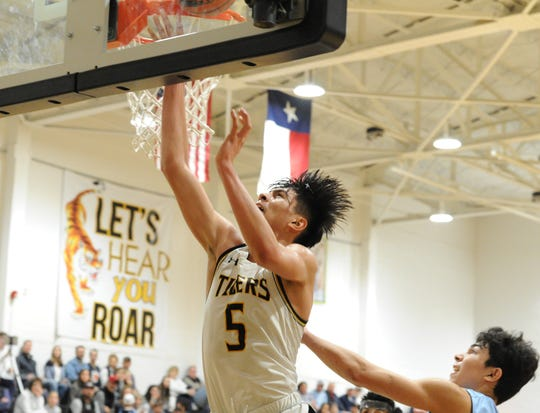 Snyder sophomore Eber Murillo (5) converts a layup against Midland Greenwood on Saturday, Feb. 8, 2020, at Tiger Gymnasium in Snyder.