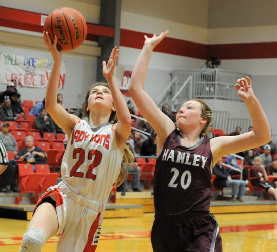 Albany senior Carley Green (22) goes for a layup as Hawley's Kyla Porter defends on Friday, Feb. 7, 2020, at Albany High School.