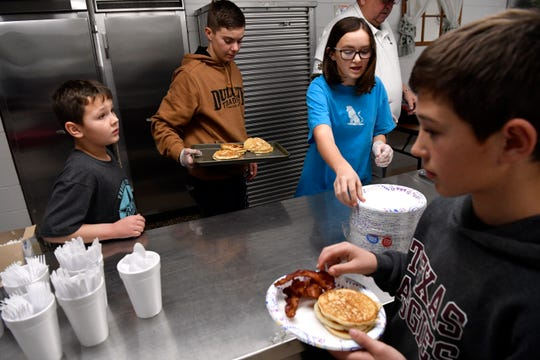 Hunter Lawrence, 11, takes his pancakes as Autry Perkins prepares to serve another plate to a customer during a pancake supper Jan. 31 at Comanche High School. The local Fellowship of Christian Athletes huddle is raising money to send some of its members to a summer camp in Lubbock.