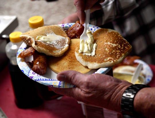A customer slathers butter onto pancakes.