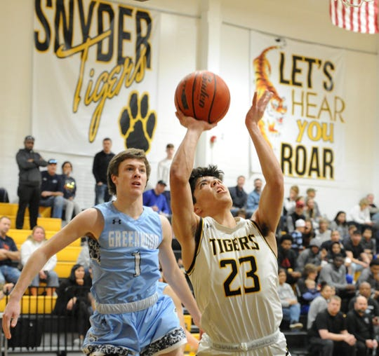 Snyder senior Jayden Samaniego (23) goes for a shot against Midland Greenwood on Saturday, Feb. 8, 2020, at Tiger Gymnasium in Snyder.