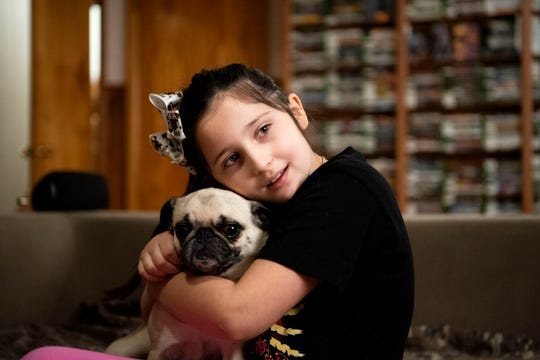 """Lillian Archie, 8, cuddles her dog on Saturday, Feb. 8 at her father's home in Battle Creek, Mich. Justin Archie is a single dad who posts """"Game of the Day"""" reviews with his daughter, bonding over the games he grew up playing."""