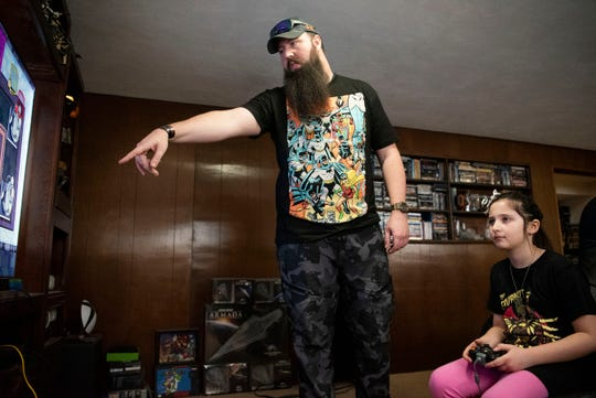 Justin Archie and his daughter Lillian Archie, 8, play an Adventure Time game on the Xbox on Saturday, Feb. 8 at their home in Battle Creek, Mich.